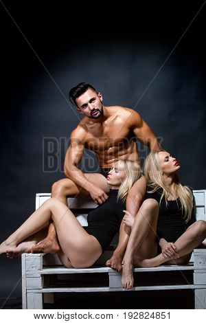 sexy blonde twin girls and athletic man with muscular wet body and strong torso in underwear pants and bodysuit on black background lesbian and gay homosexual seduction and foreplay love relations
