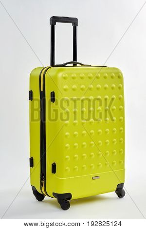 Textured wheeled luggage bag. Personal plastic suitcase isolated on white. Business trip by plane.
