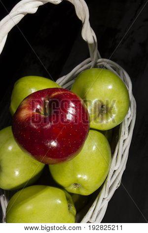 Ripe apples in a wicker basket on a black background
