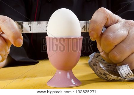 Egg in the holder and hands of the cook with a tape measure