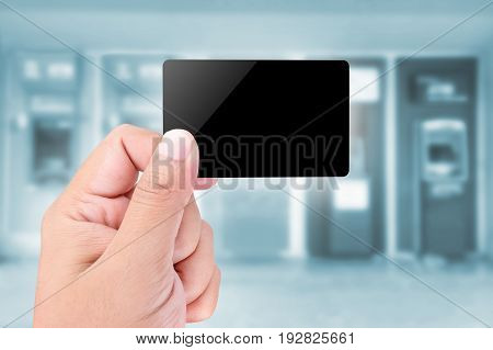 Credit Card held by hand on blurred abstract background of ATMs Machine