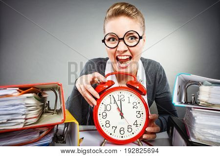 Paper work against time. Young expressive woman in office with big red clock. Crazy happy businesswoman close to ending her work.