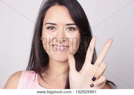 Young beatiful caucasian woman counting three over white background. Hand counting three fingers.