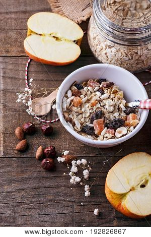 Bowl of healthy gluten free muesli with nuts and dried berry over rustic wooden background. Clean eating Vegan Vegetarian Healthy living Gluten free food concept