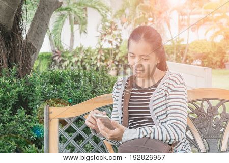 Beautiful Woman Using Smartphone For Business In The Park. Concept Technology Business.