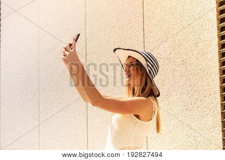 Technology internet social media concept. Young woman wearing sun hat taking picture of herself selfie with smartphone camera. Outdoor shot on sunny summer day