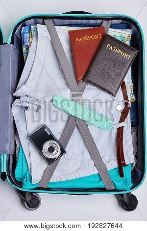 One part of opened suitcase. Passports, camera, clothes in travel bag. Concept of vacation.