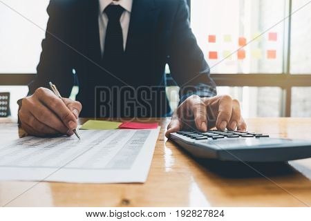 Close Up, Business Man Or Lawyer Accountant Working On Accounts Using A Calculator And Writing On Do