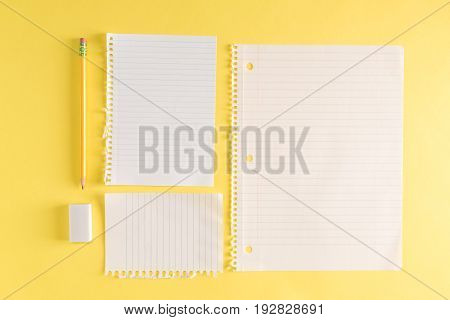Blank sheets of paper with a pencil on a yellow background