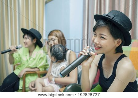 beautiful asian younger woman singing karaoke song at home family relaxing and happy time