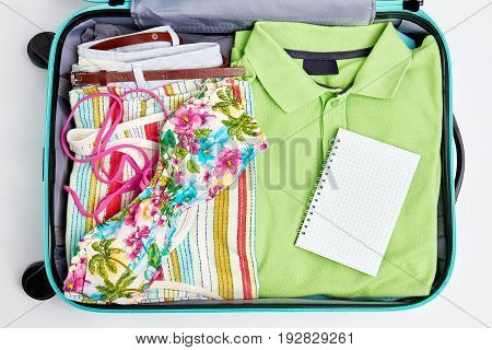 Luggage with clothing and notebook. Summer beach stuff in suitcase close up.