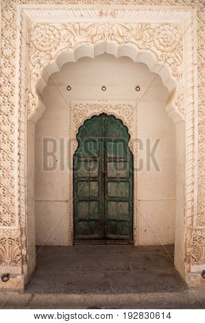 Jophpur India - 19 March 2017: Vintage Closed green gate behind an engraved wall at the Mehrangarth fort in the city of Jodhpur India