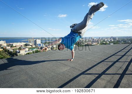 Roofer stands on his hands on the edge of the roof. Extreme acrobatics. Courage and adrenaline. Parkour and Roofing.