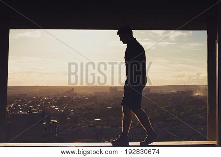 A lonely roofer on the roof of the high-rise at sunset. Courage and adrenaline. Loneliness and calmness