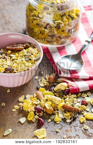 Tasty homemade muesli with nuts on old kitchen table.