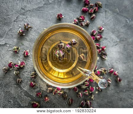 Healthy aromatic tea with dogroses buds, some buds scattered on the table, freshly brewed, topvivew