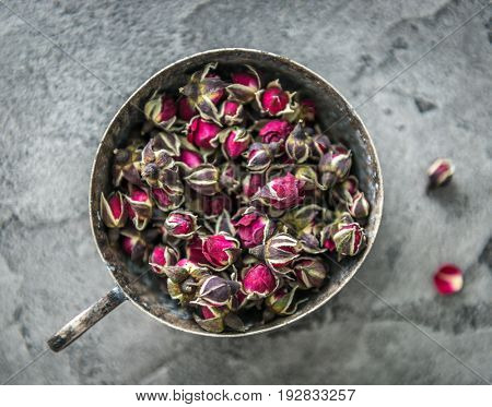 Rustic metal cup full of buds of dog roses, lovely red buds, topview