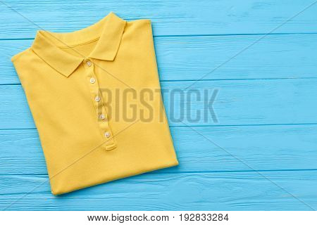 New polo t-shirt, wooden surfsce. Summer sporty clothing for casual wear.