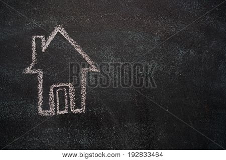 House with copyspace drawn with white chalk on blackboard