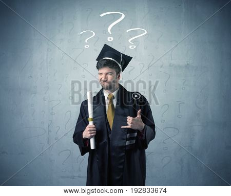Young graduate teenager with question marks drawn over his head