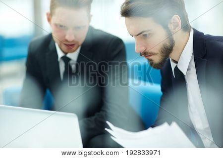 Serious manager listening to colleague explanation and reading online data