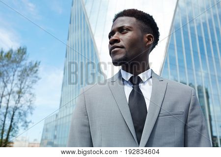 Young employee in grey suit and tie