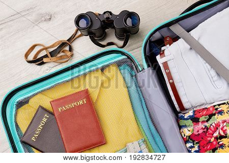 Full suitcase, passports, binocular. Close up of accessories for interesting summer trip.