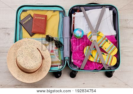 Tourist travel bag full of clothing. Essential summer stuff for positive leisure.