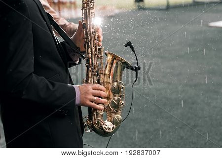 Man with a saxophone stands under rain on a green background.
