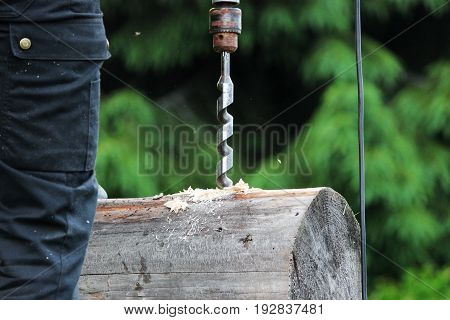 The worker collects the frame and drills a hole in a log for dowel using a drill when building a wooden house.