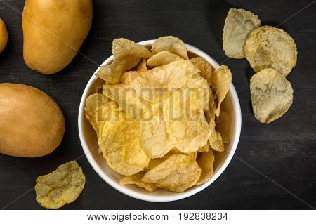 A photo of a bowl of potato chips with potatoes, shot from above on a black texture with a place for text