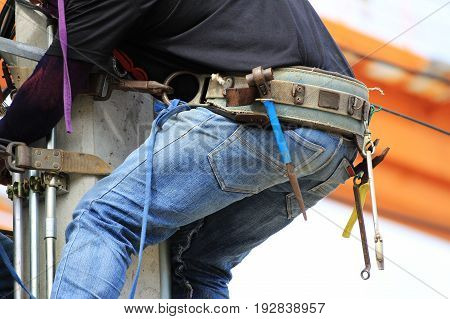 Tool Belt wearing by Electrician Climbing on Concrete Pole