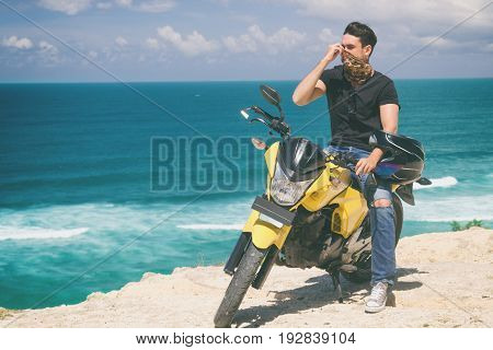 Modern handsome man posing with his motorbike.