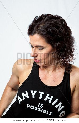Profile of a fit and muscular woman looking down and to the side. Three quarters shot on white background.