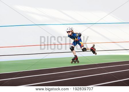 Roller skating little girl in track rollerblading on inline skates