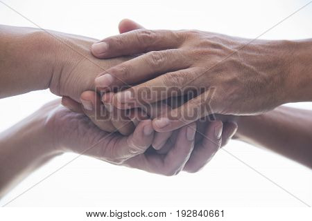 A man holding another man's hand for sympathy