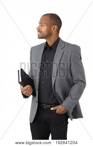 Portrait of elegant ethnic businessman with personal organizer, side view, cutout on white.