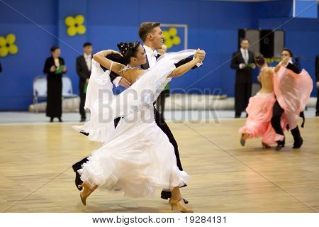 TOMSK, RUSSIA - FEB 14 : Couple dancing - Babenkov Vladislav, Tyu Kristina  (no 64) at sport dance competition of Tomsk region on February 14, 2011 in Tomsk, Russia.