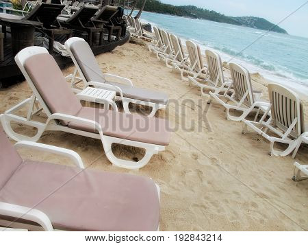 close up sandy beach with chaise lounge chairs in tropical island of Thailand