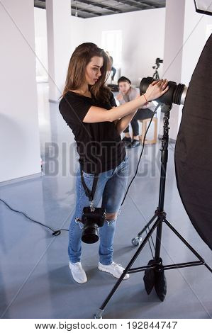 Young female photographer work in studio. Beautiful woman with camera is setting photographing equipment in studio getting ready for a photo shoot