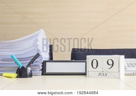 Closeup white wooden calendar with black 9 july word on blurred brown wood desk and wood wall textured background in office room view with copy space selective focus at the calendar