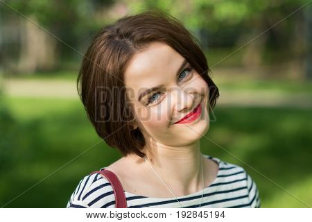 Young smiling caucasian woman outdoors portrait. Soft green background. Close-up portrait.