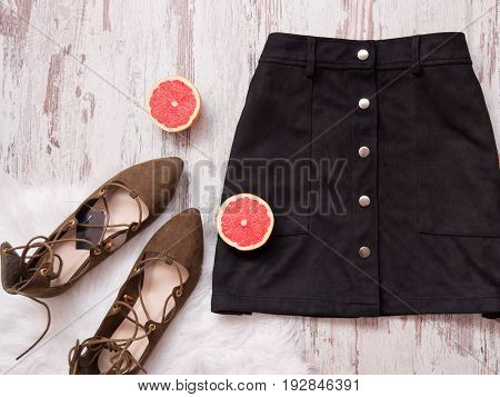 Black Suede Skirt, Brown Suede Shoes, Cut Grapefruit Halves. Wooden Background. Fashion Concept. Top