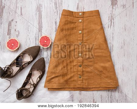 Brown Suede Skirt, Brown Suede Shoes, Cut Grapefruit Halves. Wooden Background. Fashion Concept. Top