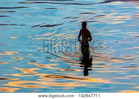 silhouette of a fisherman in abstract reflection of water ripples