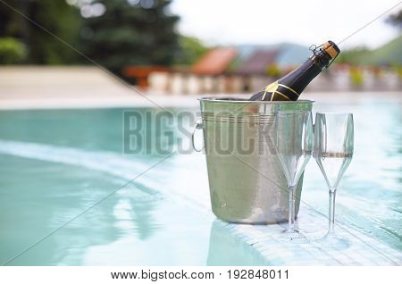 Ice bucket champagne bottle and two glasses near smimming pool