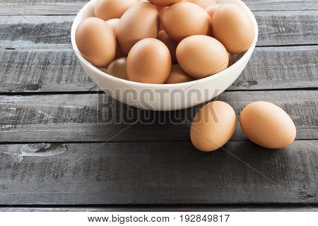 Fresh hen egg in white bowl and 2 hen egg out side on Black color wood table