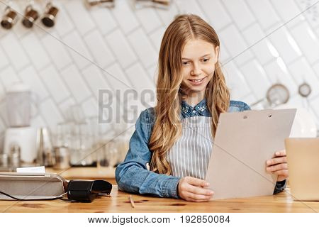Careful examination. Charming fair-haired teenage girl standing behind a bar counter, holding a newly-printed menu of cafe and studying it thoroughly