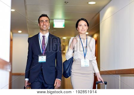 business trip and people concept - man and woman with travel bags and conference badges at hotel corridor