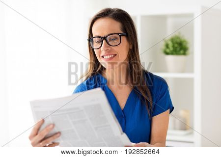 business, people and mass media concept - happy smiling woman in glasses reading newspaper at office